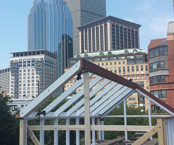 The Boston city skyline stretches to the sky behind the glass roof frame being installed and assembled by Sunspace Design