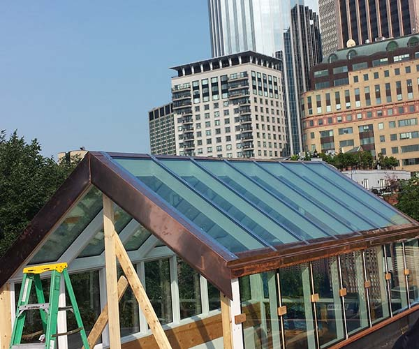 Copper capping and flashing work continues on all sides of this Boston, Massachusetts glass roof structure construction site