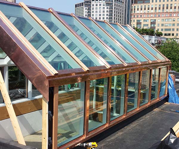One side of the structure is fully complete; the clerestory walls and sloped roof glimmer in the sunlight thanks to the addition of copper flashing