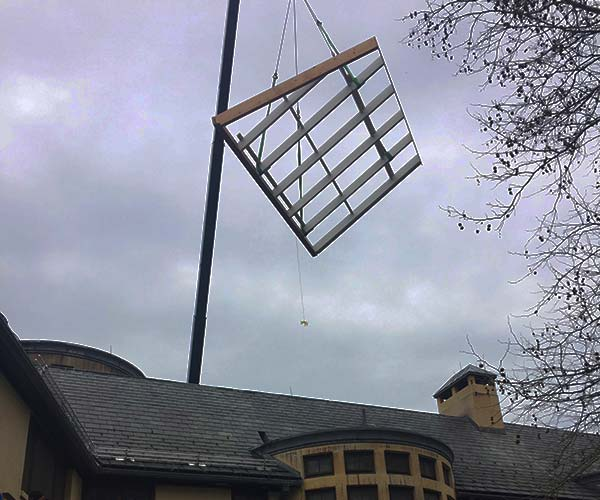 A crane lifts the roof frame of the new conservatory over the Weston, MA estate and into position