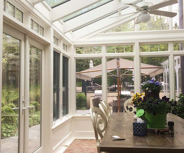 The conservatory is outfitted with Anderson 400-series windows and outswing French doors leading to a beautiful patio space