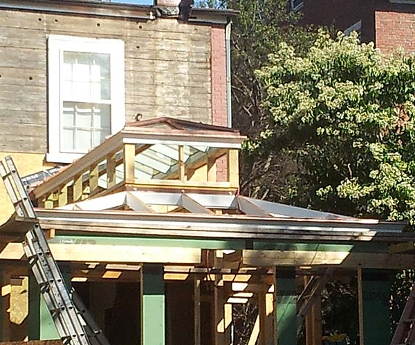The solid wood conservatory roof system frame has been assembled, but no glass has been installed at this stage of construction