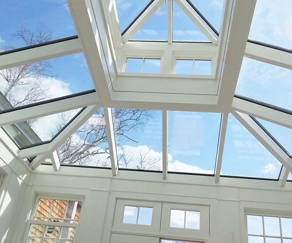The bright morning sky is visible through the glass roof elements of this Salem conservatory project