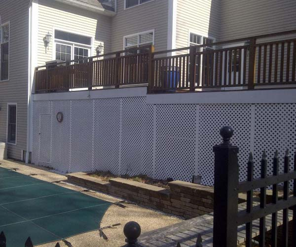 The backyard parking lot and raised deck of a Dover, Massachusetts home