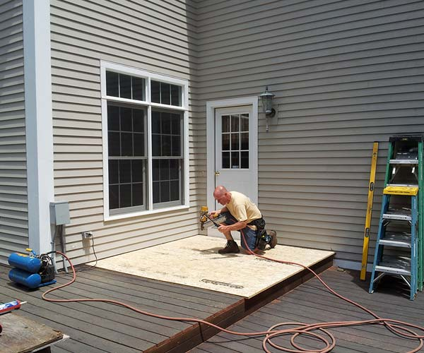 "A Sunspace crewman installs 3/4"" Advantech plywood to protect and make use of the existing deck surface"