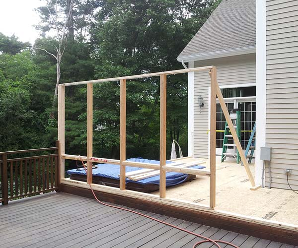 A single wall of the new sunroom addition has been raised atop the existing deck space