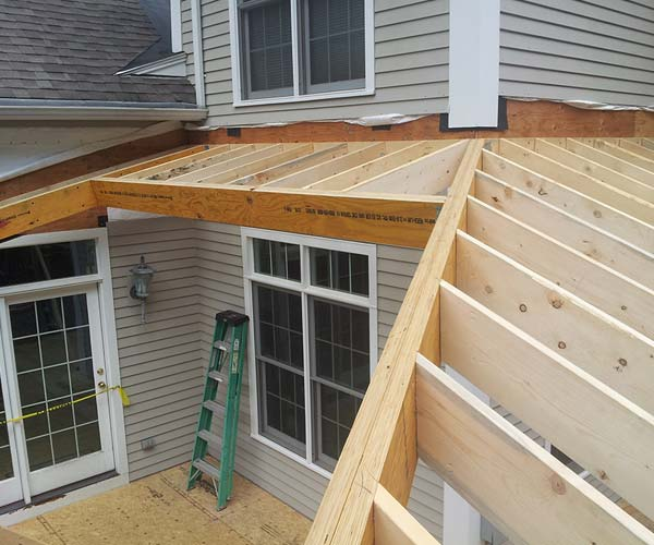 The complicated sunroom glass roof frame comes together around the bend of the home