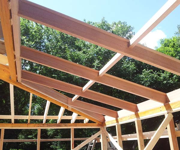 The custom mahogany sloped glazing unit frame has been installed before the glass is brought in