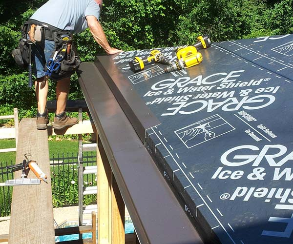 A Sunspace worker installs flashing that wraps continuously around the roof sections