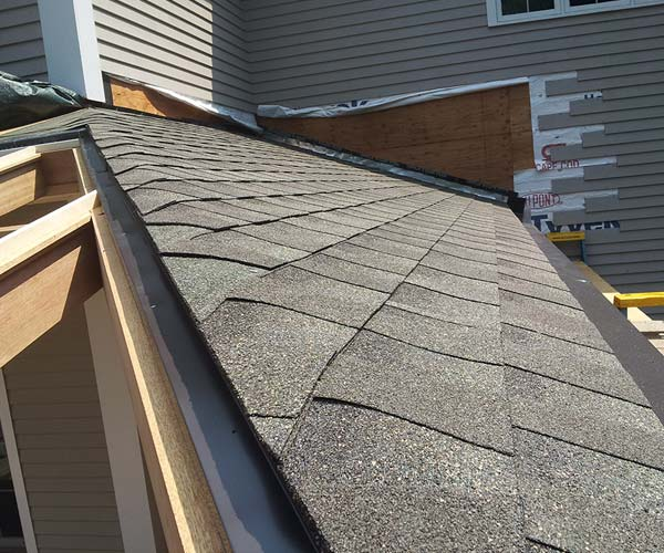 The solid roof section with conventional roofing shingles meets the glass roof frame at the hip of the enclosure