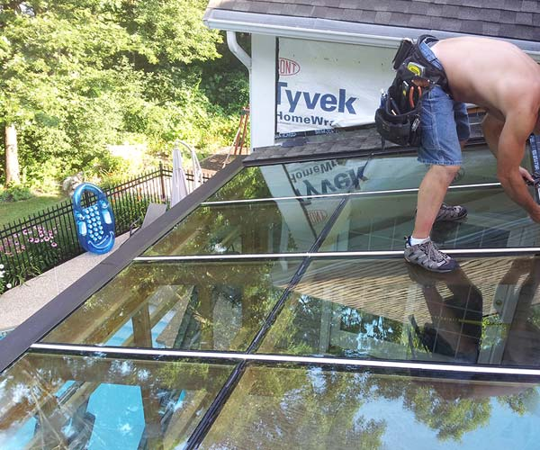 Our crewmen install bronze aluminum flashing to blend perfectly with the dark asphalt roof shingles adjacent to the glass roof section