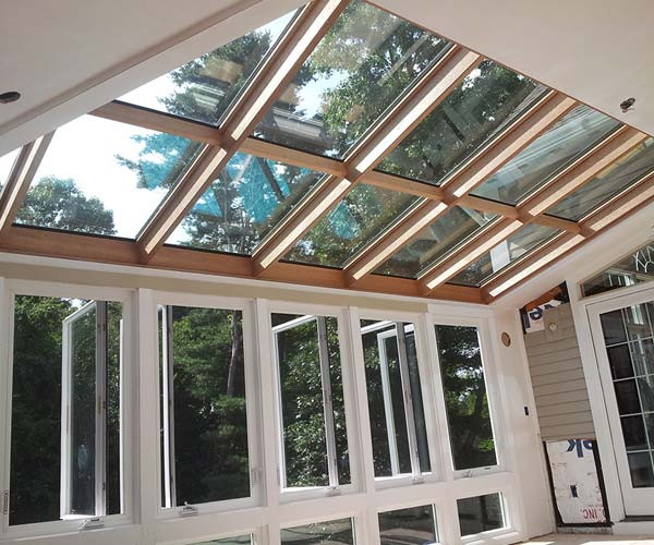 The sloped glazing system introduces magnificent levels of natural sunlight into the sunroom addition