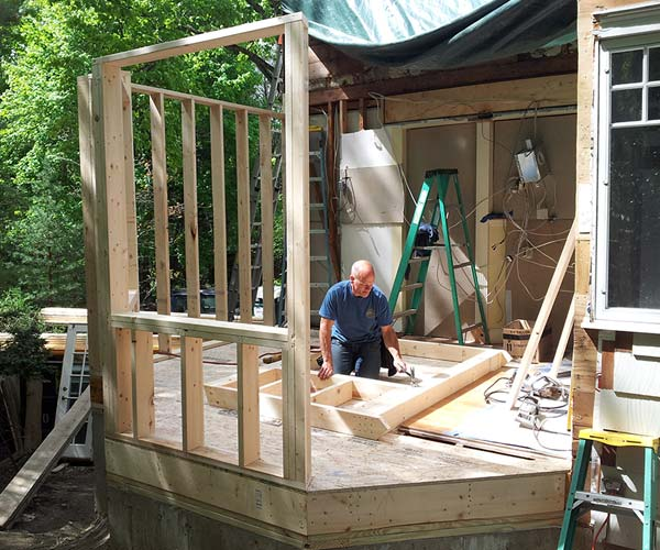 A Sunspace Design crewman works in the middle of the new extension which features new wall frames on multiple sides