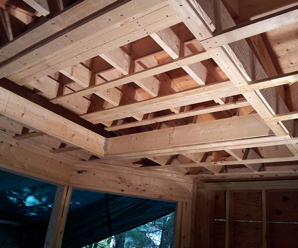 The roof frame contains visible structural elements that will create a recessed tray in the finished space