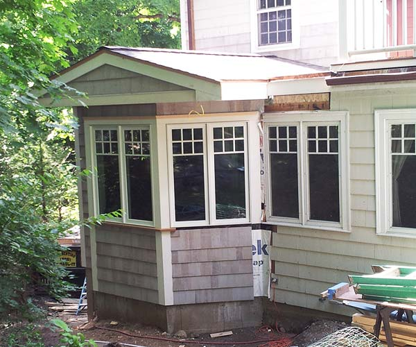 An exterior view of a kitchen extension that shows the siding at 90% completion and weather sealing behind the uncompleted portions