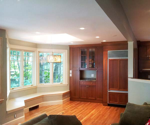 A finished, well-lit photo of the Belmont, Massachusetts kitchen construction project with hardwood flooring, a beautiful light fixture, and custom cabinets