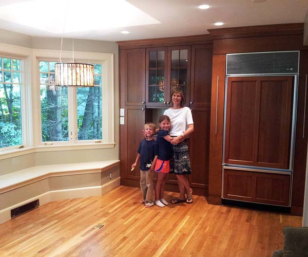 A client and her two happy children stand in their new kitchen extension featuring hardwood floors, bright windows, and custom cabinets
