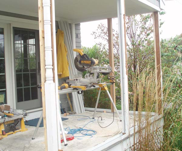 Construction equipment rests on a protected work area as railings and ready posts are removed from the walls of the porch