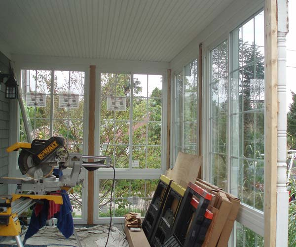 The interior of this three-season porch enclosure is partially finished, with tall windows lining the walls