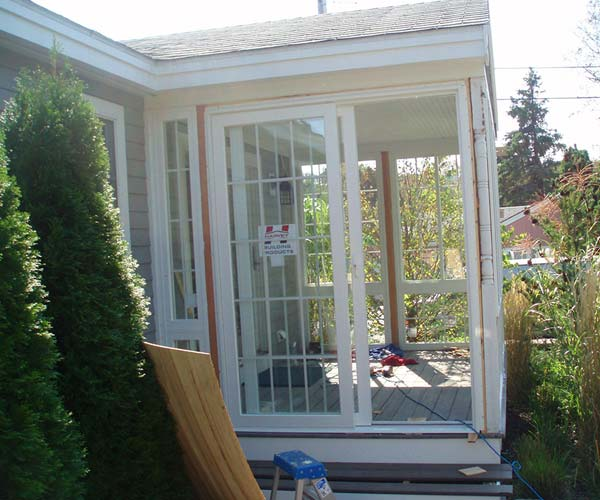 Brand new sliding glass doors have been introduced to the side entry of this enclosed porch