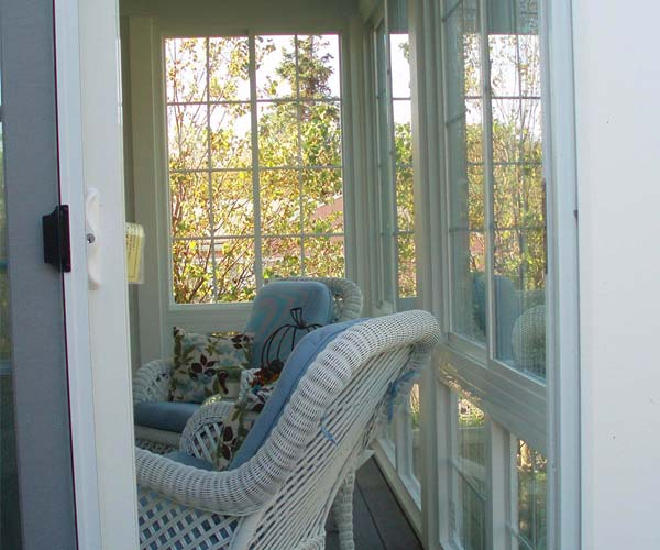 A relaxing seating area visible through the open sliding doors of a porch enclosure