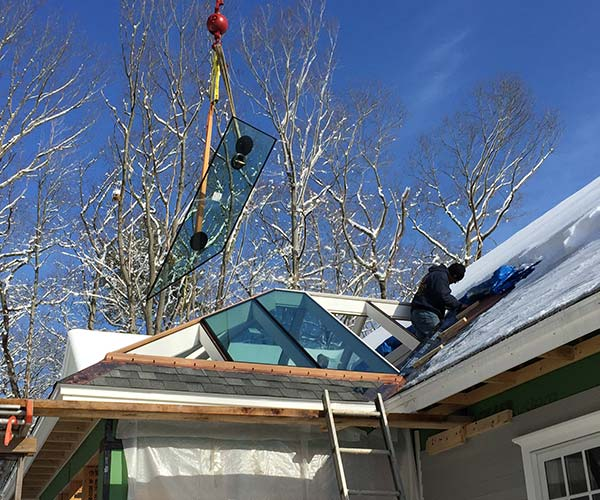 Sunspace Design crewmembers are hard at work installing new glass panes in the glass roof of a stunning Rye, New Hampshire conservatory