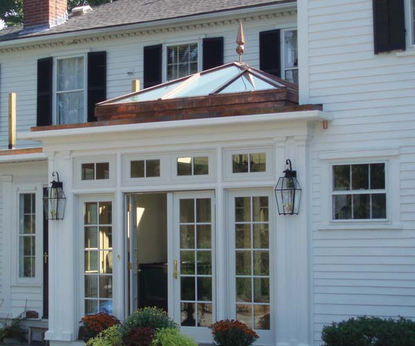 A photo taken of a colonial orangery located in Shrewsbury, Massachusetts in which a decorative finial can be seen adorning the custom glass roof
