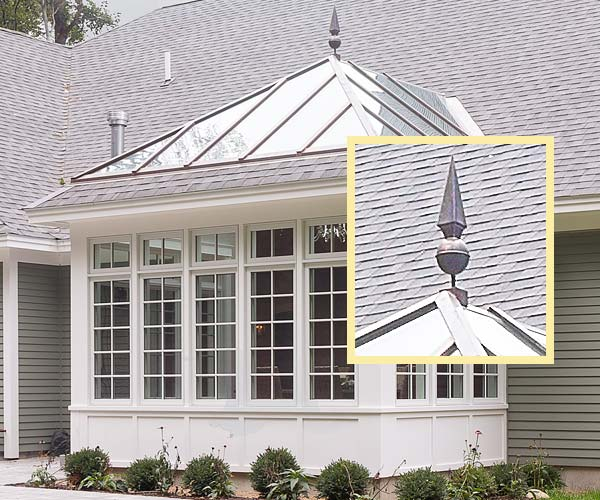 A photo of a custom glass conservatory built by Sunspace Design in Rye, New Hampshire depicting a bold decorative finial atop an angular glass roof