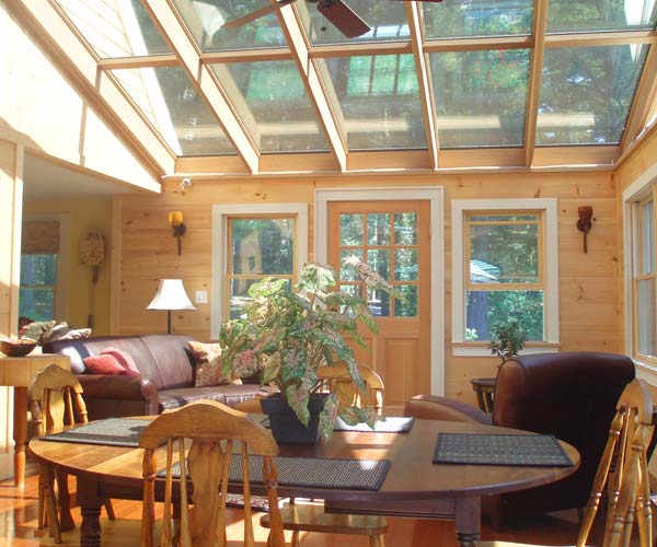 This photo of a rustic sunroom from Gloucester, Massachusetts features large glass roof elements transmitting light to an open concept seating, dining, and kitchen space