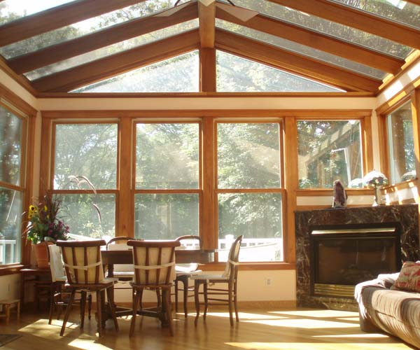 A warmly-lit Newton, Massachusetts sunroom with a small seating area, large windows, a gable roof, and a luxurious fireplace