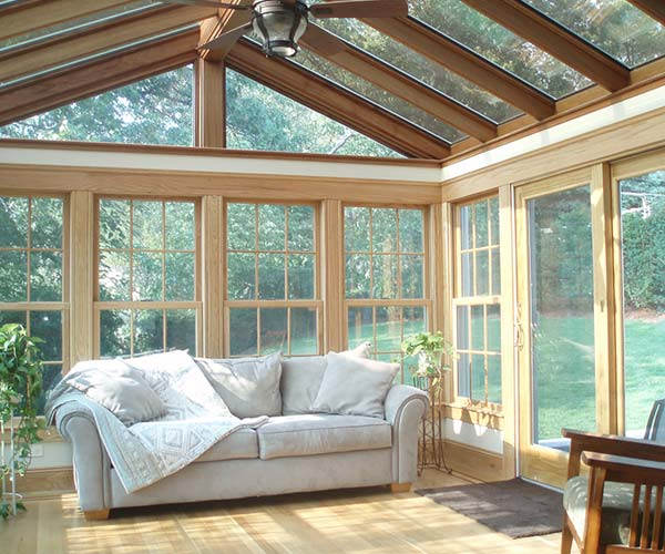 A comfortably warm sunroom with a nice couch, reading chair, large windows, and sliding doors in Arlington, Massachusetts