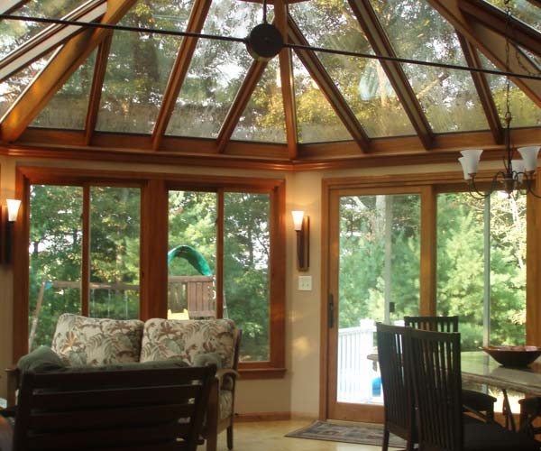 A Sharon, Massachusetts glass and wood conservatory with a complex roof system and doors opening to an exterior wraparound deck