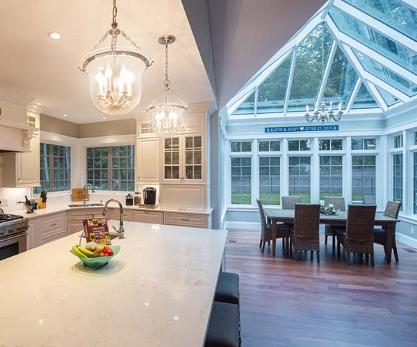 The angular glass roofed conservatory featured here is adjacent to the Rye, New Hampshire home's large kitchen