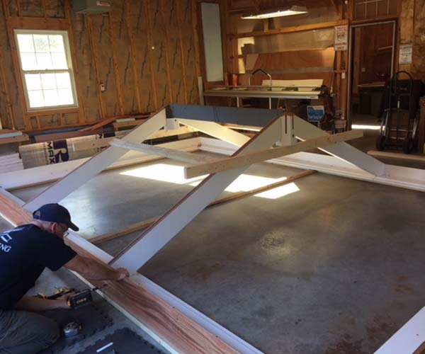 A Sunspace Design engineer assembles the conservatory's insulated glass roof system in the wood shop