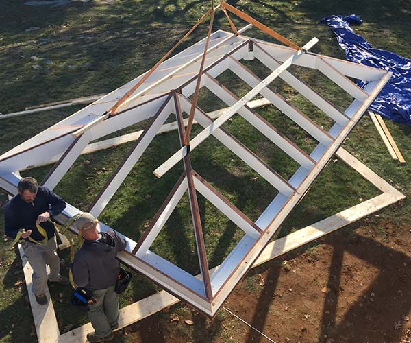 Sunspace crewmen secure the straps that the crane operator will use to lift the mahogany roof frame into position above the conservatory