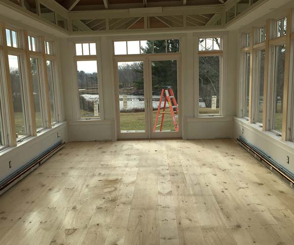 Wide pine floorboards have been installed in the conservatory to achieve a beautiful, rustic effect