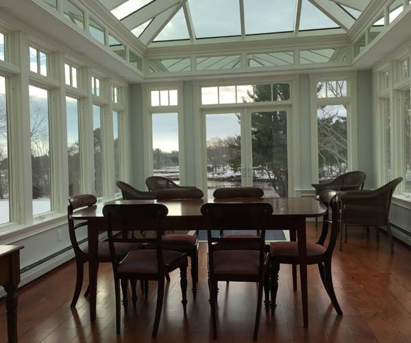 A photo from the completed conservatory's interior which shows the connection to the kitchen, a beautiful dining table, and stunning panoramic views