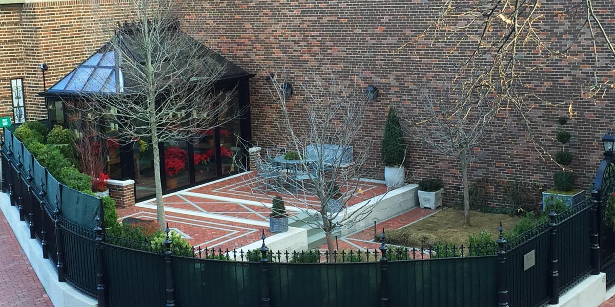 An outdoor brick and stone patio area containing a gorgeous custom greenhouse is surrounded by a wrought iron fence and a border of shrubbery