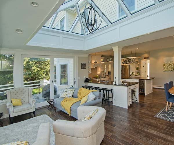 A bright, open concept kitchen located in Medfield, Massachusetts with a glass orangery-style seating area and double-hip skylight above