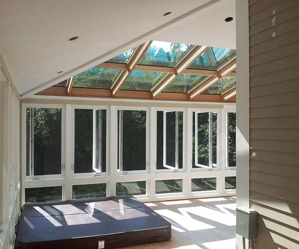 A deck-to-sunroom conversion with large glass ceiling panes and a fully functioning hot tub for relaxation and entertainment