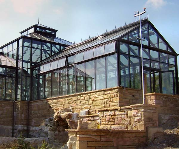 A beautiful greenhouse framed in black, powder-coated aluminum sits atop a stone foundation