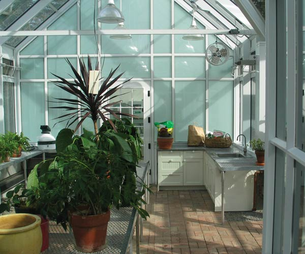 The interior of this aluminum greenhouse workspace with counters and sink is filled with plants at various stages of development