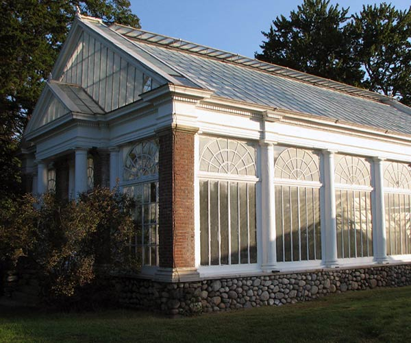 A sturdy, large greenhouse built out of stone, wood, brick, and aluminum framing stands proudly as the sun reflects along its flank