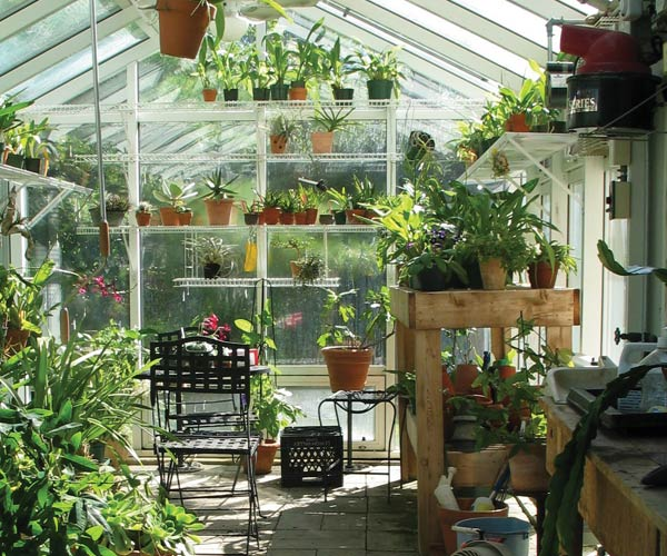 A Sunspace Design greenhouse built in Maine features fully stocked shelves, a watering area, and plenty of space for extra supplies