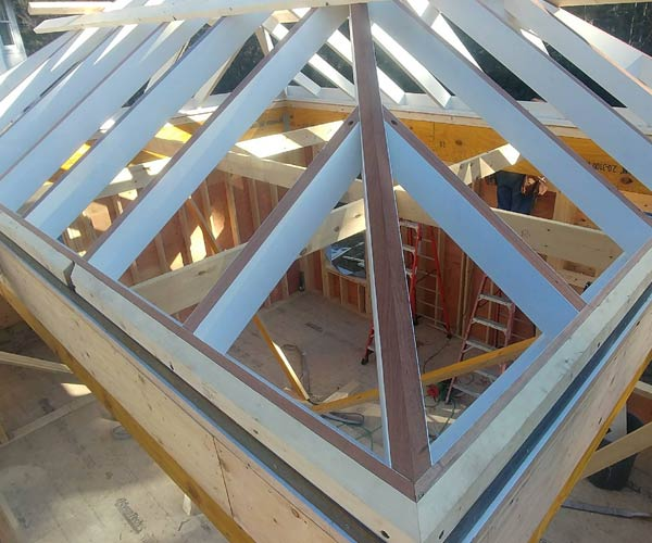 A glass roof frame (before glass installation) has been lowered onto a conventionally constructed room frame that will become a brand new glass orangery