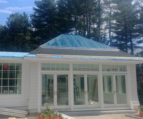 A view of a brand new orangery-style sunroom, painted white, with building materials and construction tools nearby