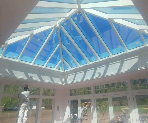 A worker diligently paints the interior of a sunroom in white while rays of sunlight penetrate the space from the brand new glass roof