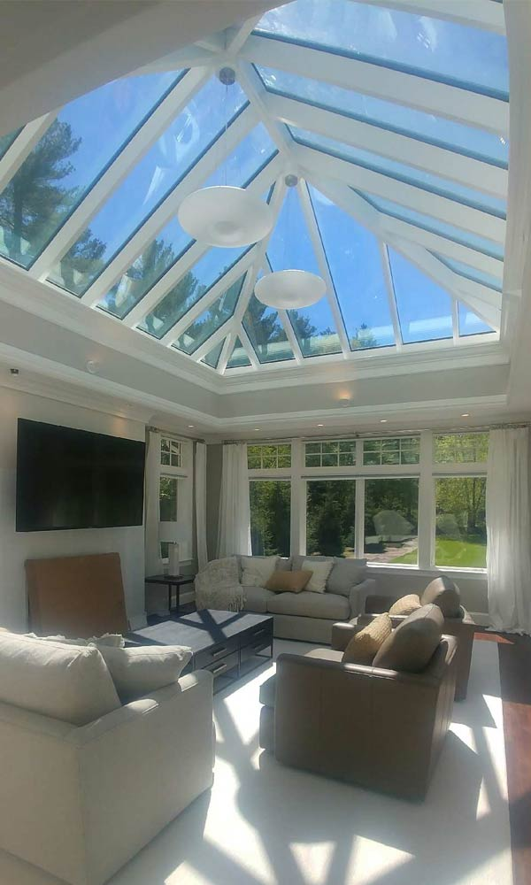 A beautiful sunroom space features an entertainment, seating, and television area that is illuminated by the sun's rays