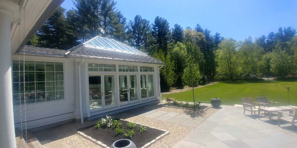 A brand new Sunspace Design glass enclosure stands proudly and glimmers in the sun beside a patio and garden area