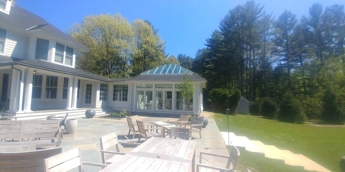 A gorgeous Concord, Massachusetts sunroom is annexed directly to this majestic residential property and also provides beautiful access to the backyard patio area